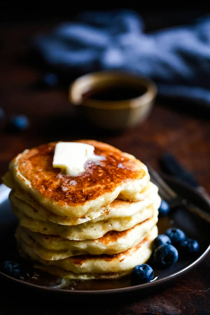 A stack of the Best Buttermilk Pancakes topped with butter on a plate with blueberries.