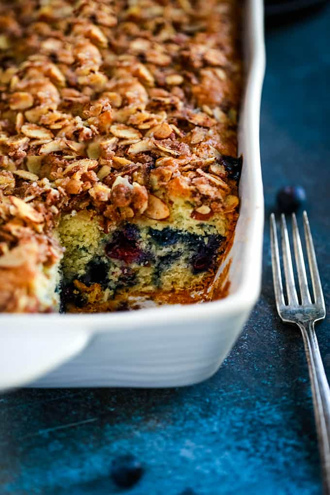 A baking dish of Blueberry Lemon Almond Coffee Cake with a slice removed.