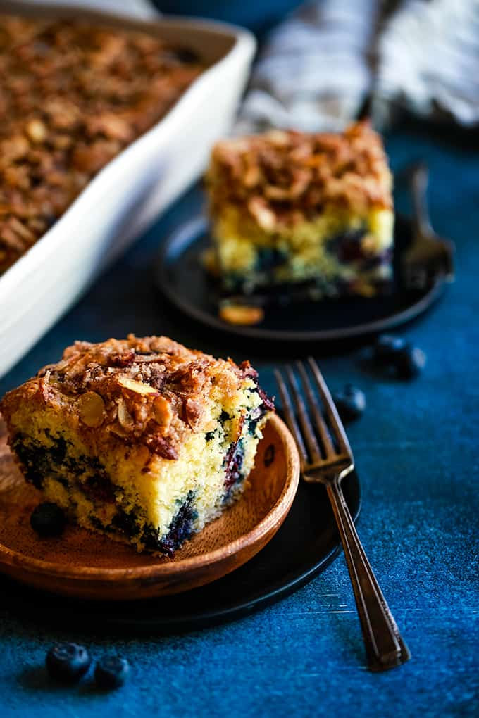 Two slices of Blueberry Lemon Almond Coffee Cake on plates next to a baking dish.