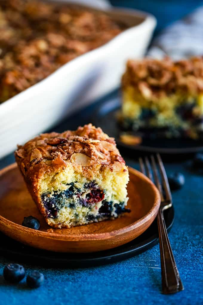 A slice of Blueberry Lemon Almond Coffee Cake on a wooden plate in front of a casserole dish.