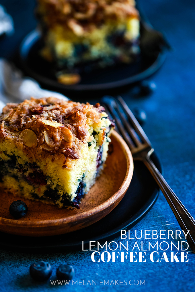 A slice of Blueberry Lemond Almond Coffee Cake on a wooden plate with a fork.
