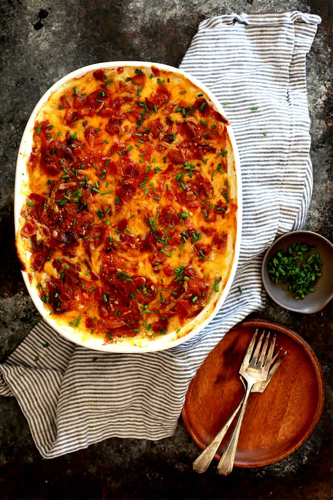 These Loaded Scalloped Potatoes are sure to steal the show at your dinner table. Sliced skin-on potatoes are layered with butter, chives, bacon and cheddar cheese. Repeat. The layers are then covered with an amazing milk and yogurt mixture to create the most delicious creamy sauce.