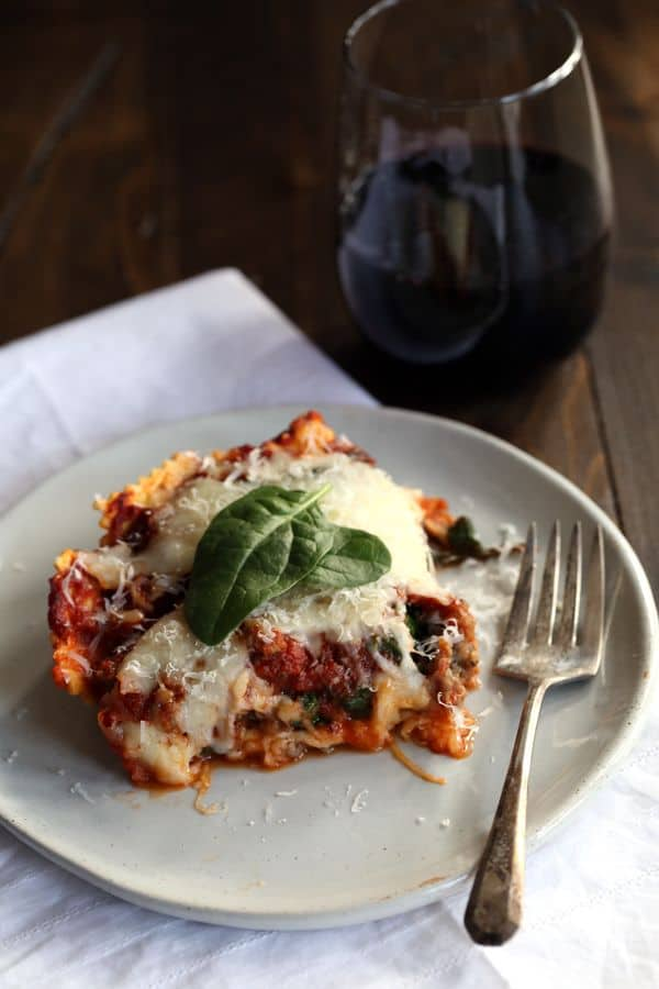 This Quick and Easy Ravioli and Spinach Lasagna is perfect for a weeknight dinner. Melty mozzarella cheese is sandwiched between two layers of ravioli to create the base of this lasagna. Topped with Italian sausage, spinach and then smothered in marinara, this five ingredient lasagna is on the table in no time!