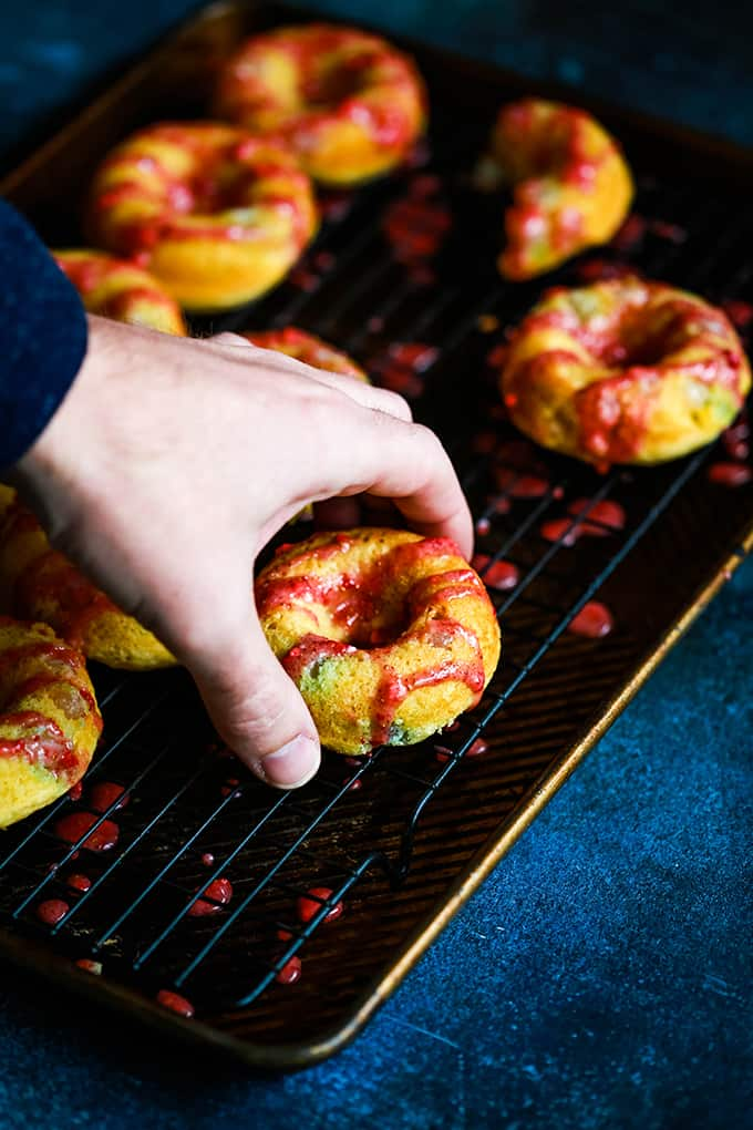 A hand grabs a Jelly Bean Donut off of a cooling rack.