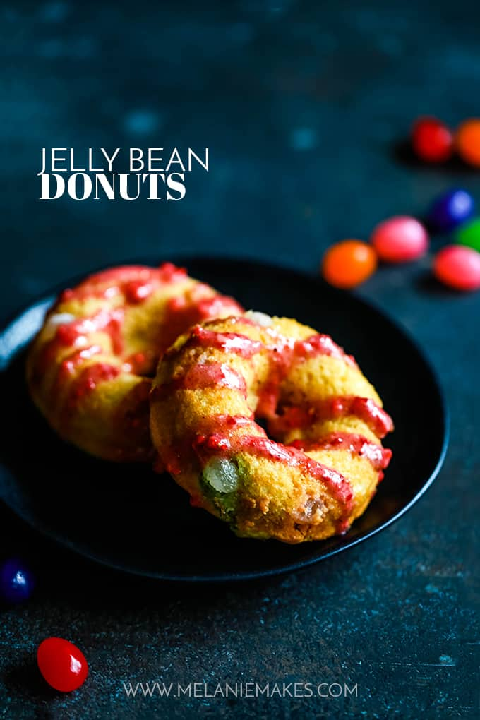 Two Jelly Bean Donuts sitting on a black plate.