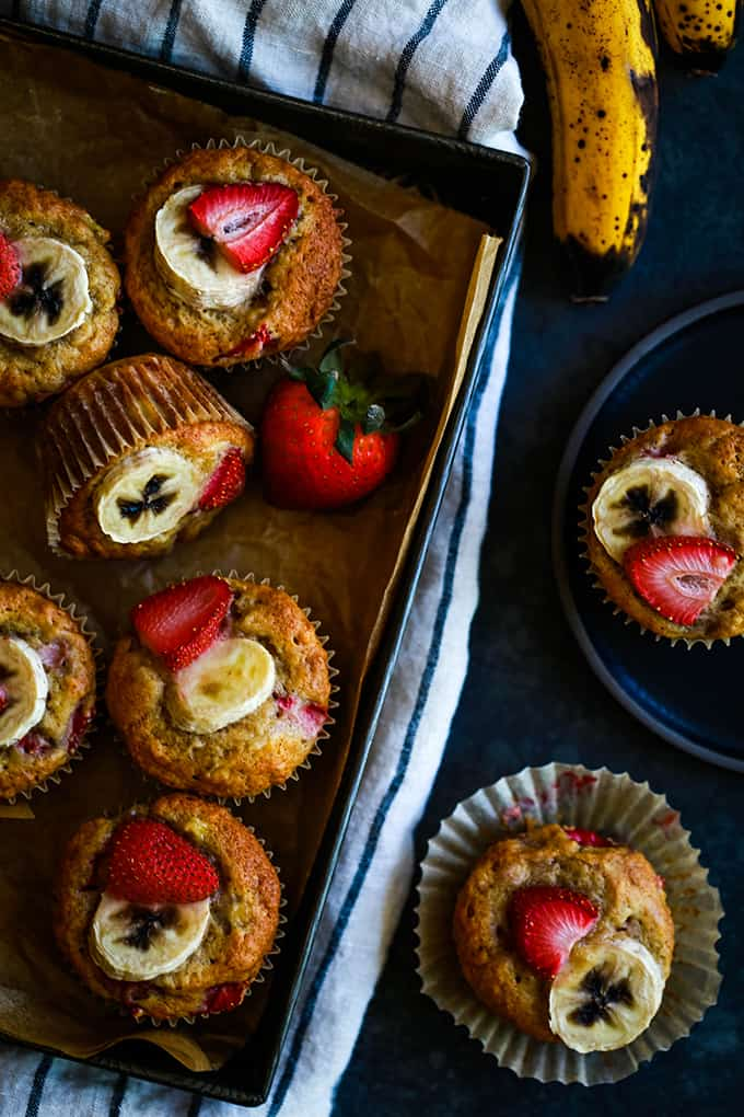 A pan of Strawberry Banana Muffins with two muffins sitting next to it.