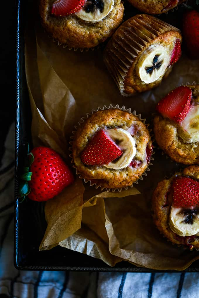 Strawberry Banana Muffins sit in a baking pan lined with parchment.