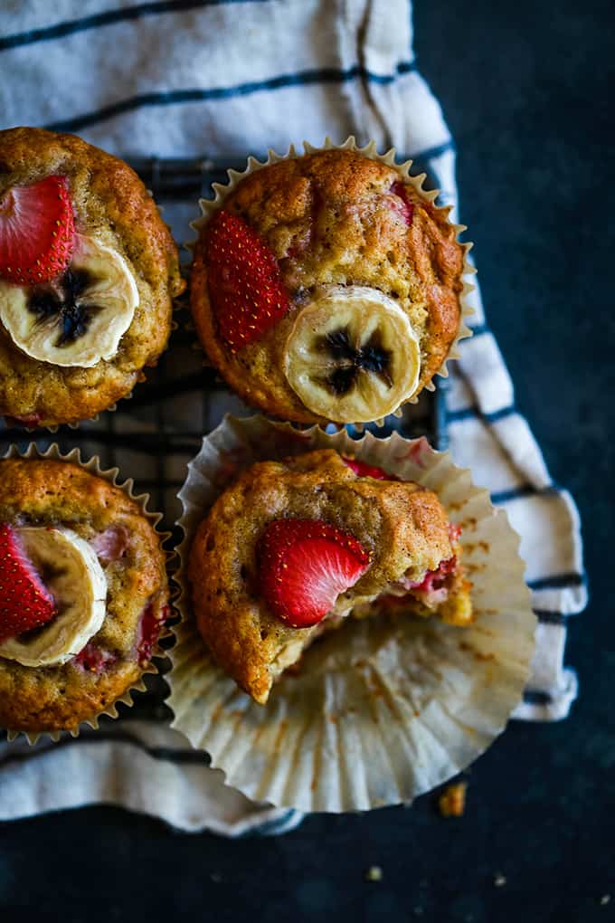 Four Strawberry Banana Muffins sitting on a striped napkin with a bite removed from one button.