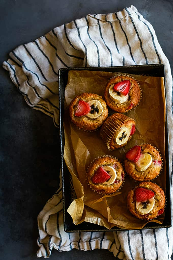 An overhead view of Strawberry Banana Muffins in a parchment lined baking pan sitting on a striped napkin.