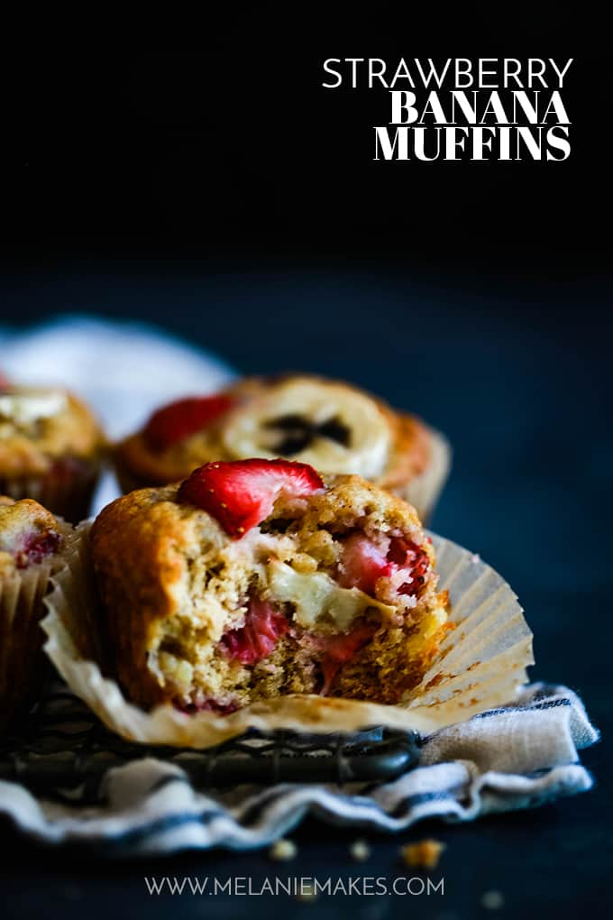 Four Strawberry Banana Muffins with a bite removed from one muffin.