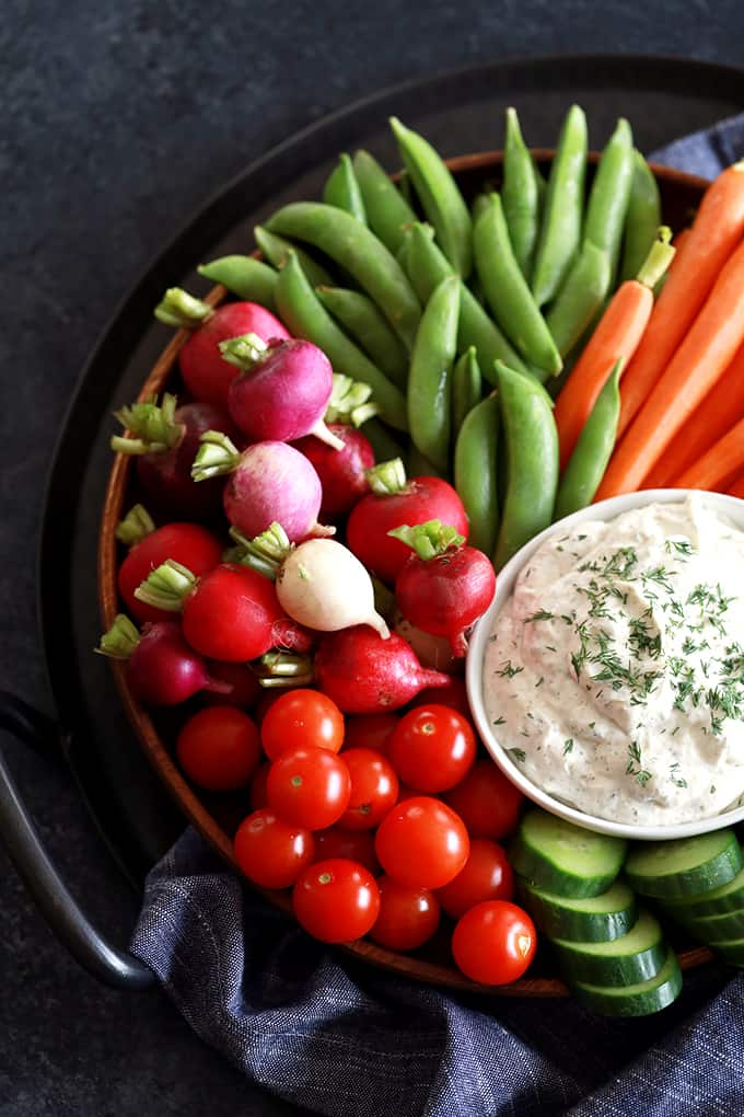 An overhead view of a bowl of Yogurt Dill Vegetable Dip on a platter of vegetables.