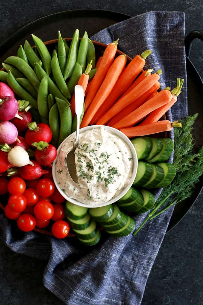A platter of vegetables with a bowl of Yogurt Dill Vegetable in the middle with a spoon.