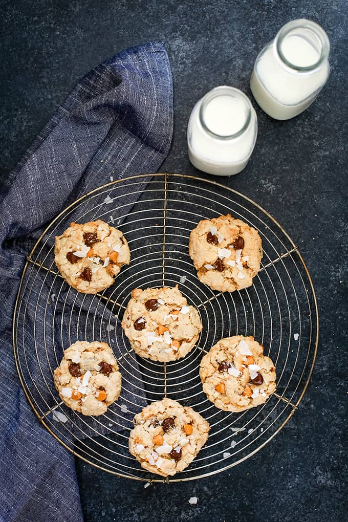 An overhead view of Magic Cookie Bar Cookies on a wire rack flanked by a napkin and two bottles of milk.