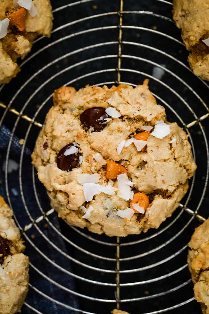 A Magic Cookie Bar Cookie garnished with coconut flakes on a wire rack.