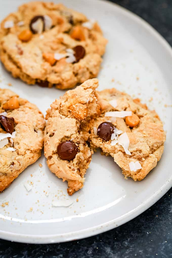 A Magic Cookie Bar cookie is split in half and sits on a plate with two additional cookies.