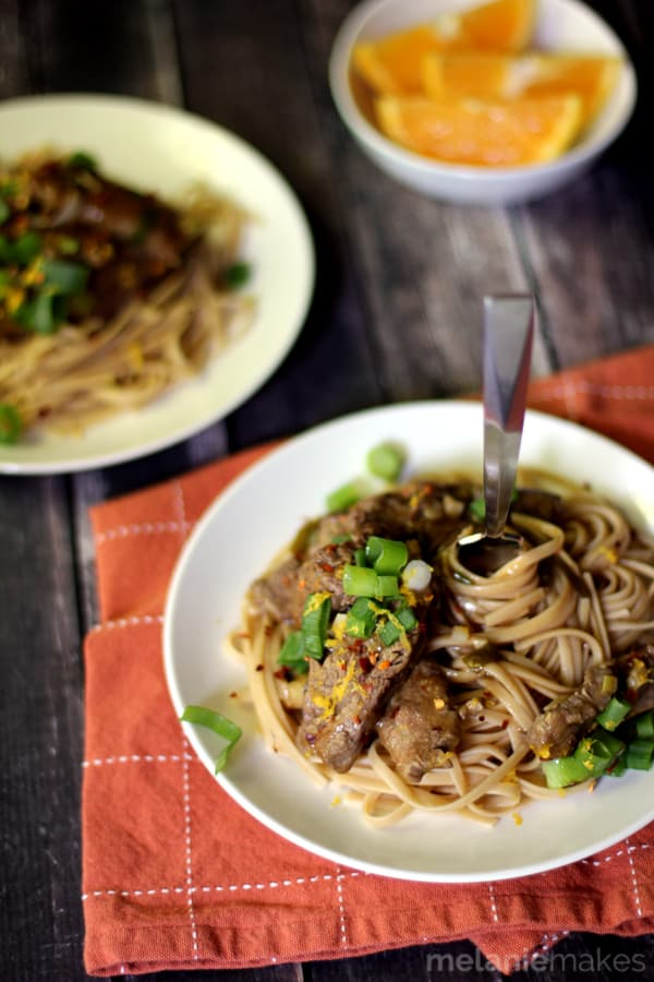 This Slow Cooker Spicy Orange Beef is the easiest fake out take-out ever! A bed of whole wheat linguine holds strips of red pepper and orange speckled strips of flank steak. A sprinkle of sliced green onions later and this is the easiest Asian inspired meal you'll ever create at home!