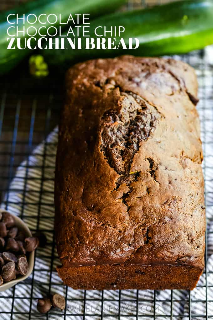 A loaf of Chocolate Chocolate Chip Zucchini Bread on a cooling rack with a striped towel underneath.