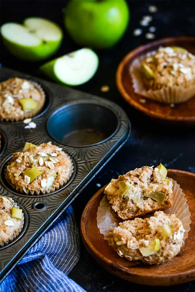 Cinnamon Apple Oatmeal Muffins in a muffin tin with a striped towel on a black background. Two wooden plates each hold a muffin and apples are alongside.