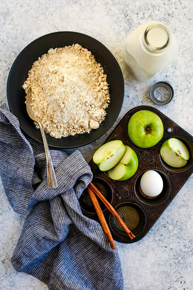 The ingredients required to make Cinnamon Apple Oatmeal Muffins on a white and grey background.