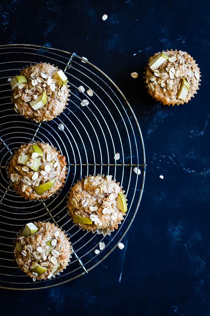 Cinnamon Apple Oatmeal Muffins on a circular wire cooling rack on a black background.