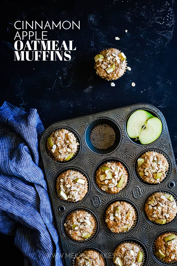 Cinnamon Apple Oatmeal Muffins in a muffin tin with a striped towel on a black background.