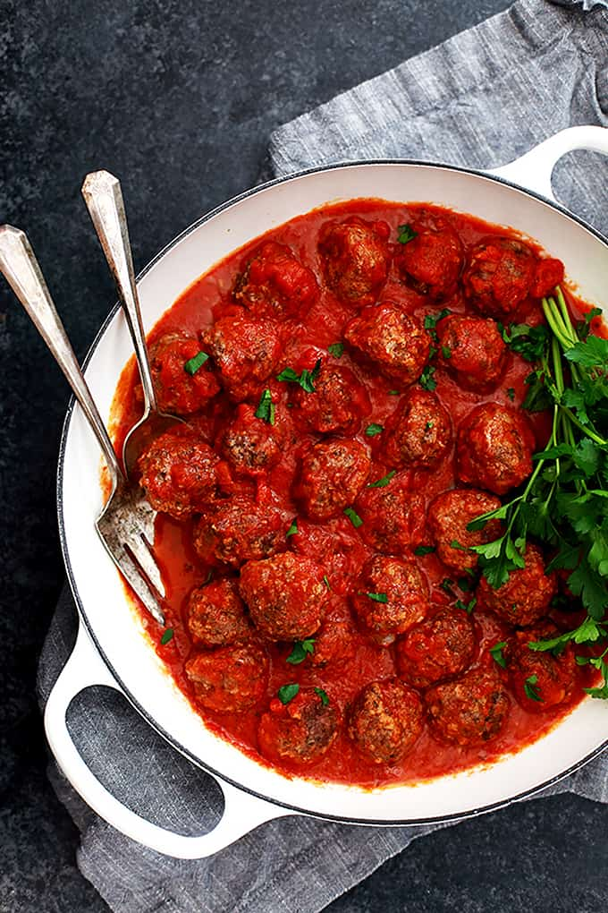 A white dish of Easy Baked Meatballs garnished with parsley and resting on a grey napkin.