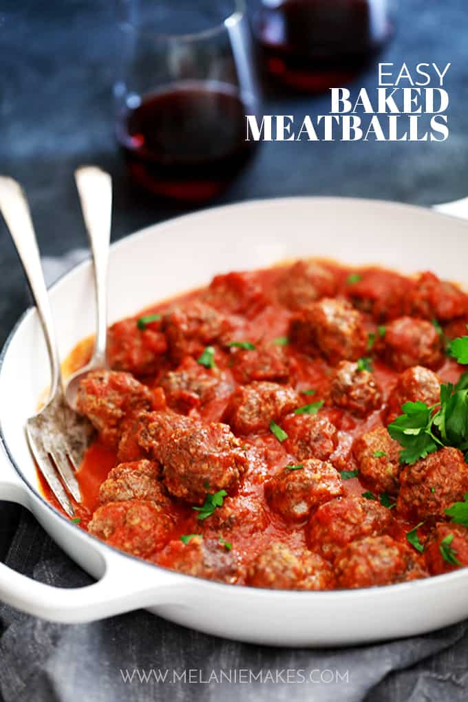 A white casserole dish of Easy Baked Meatballs with a serving spoon and fork.