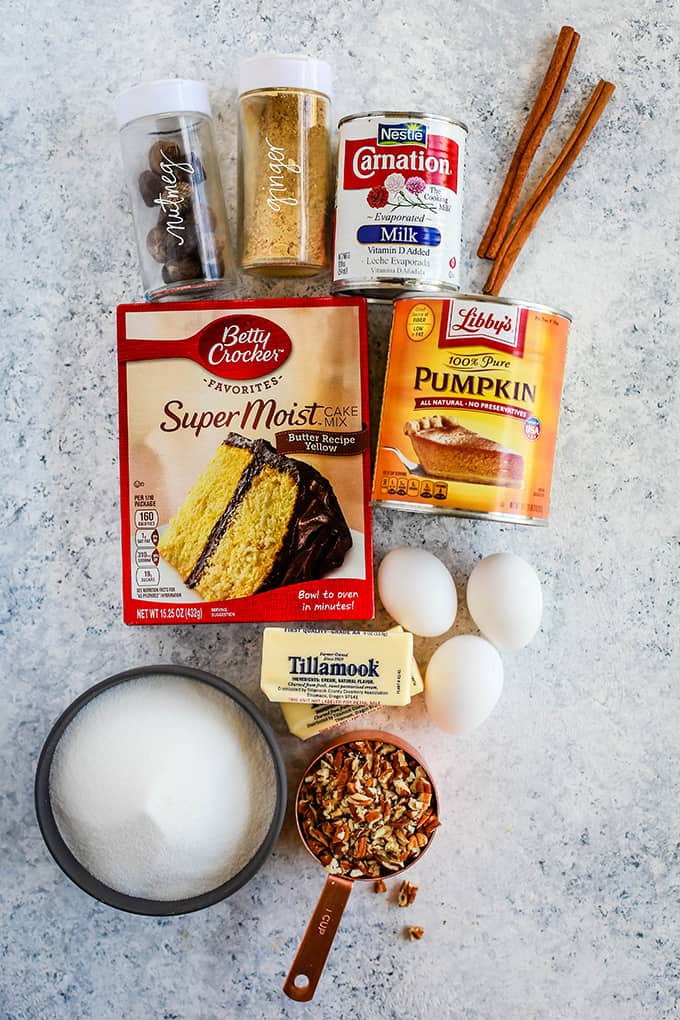 All of the ingredients needed to create Upside Down Pumpkin Pie on a white speckled background.