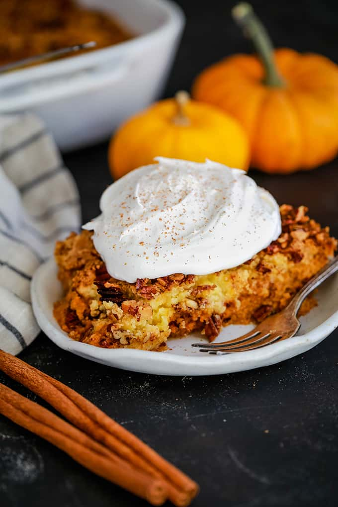 A white plate of Upside Down Pumpkin Pie topped with whipped topping is surrounded by cinnamon sticks, a striped napkin, two mini pumpkins and a white casserole dish.
