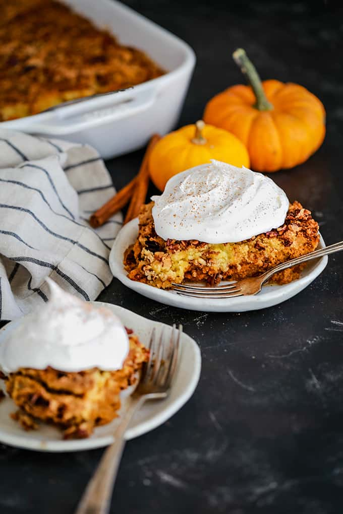 Two white plates of Upside Down Pumpkin Pie topped with whipped topping are surrounded by two mini pumpkins, a striped napkin and a serving dish.