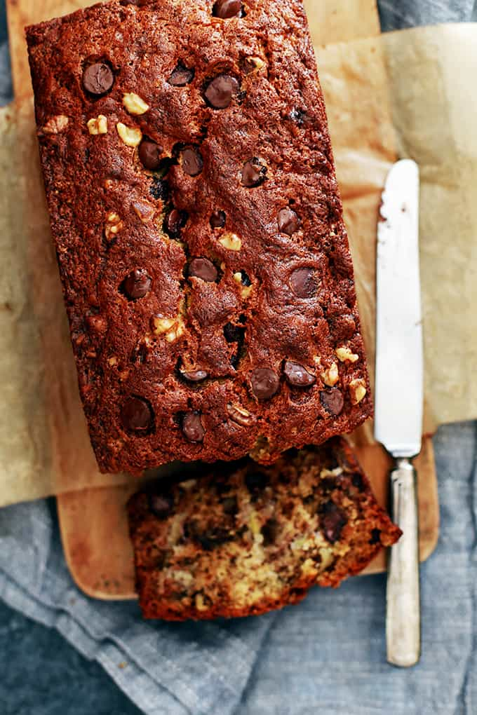 An overhead photo of a loaf of Chocolate Chip Walnut Banana Bread sitting on a wood cutting board surrounded by a knife and grey napkin.