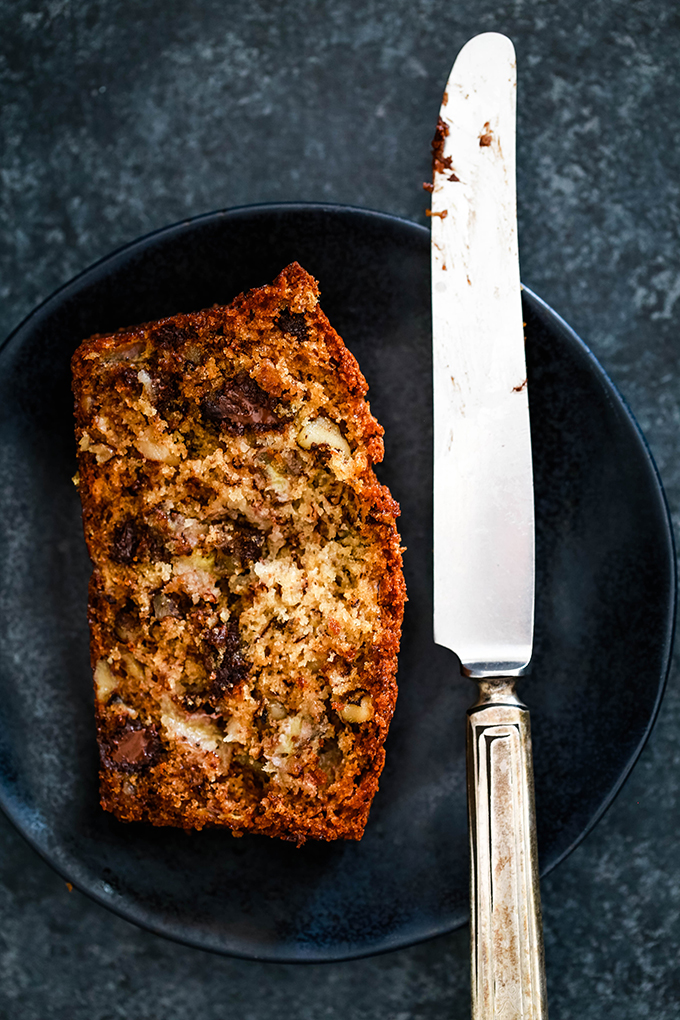 A slice of Chocolate Chip Walnut Banana Bread sits on a black plate with a knife.
