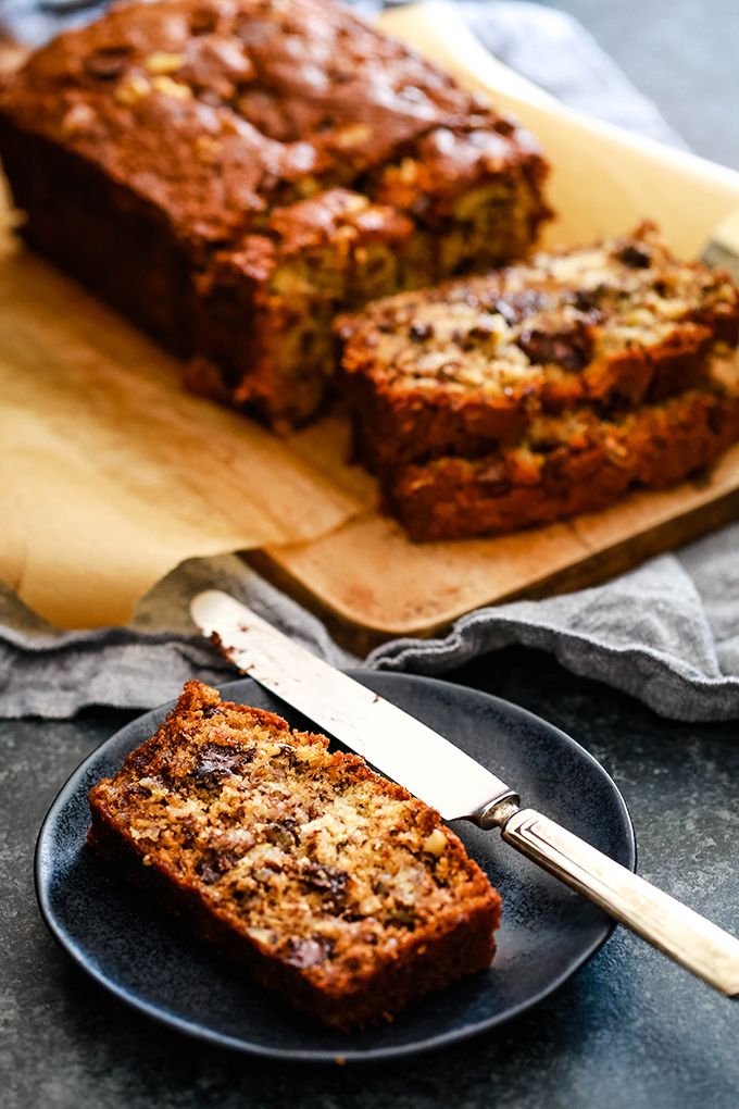 A piece of Chocolate Chip Walnut Banana Bread sits on a black plate with a knife and the sliced loaf sits behind it.