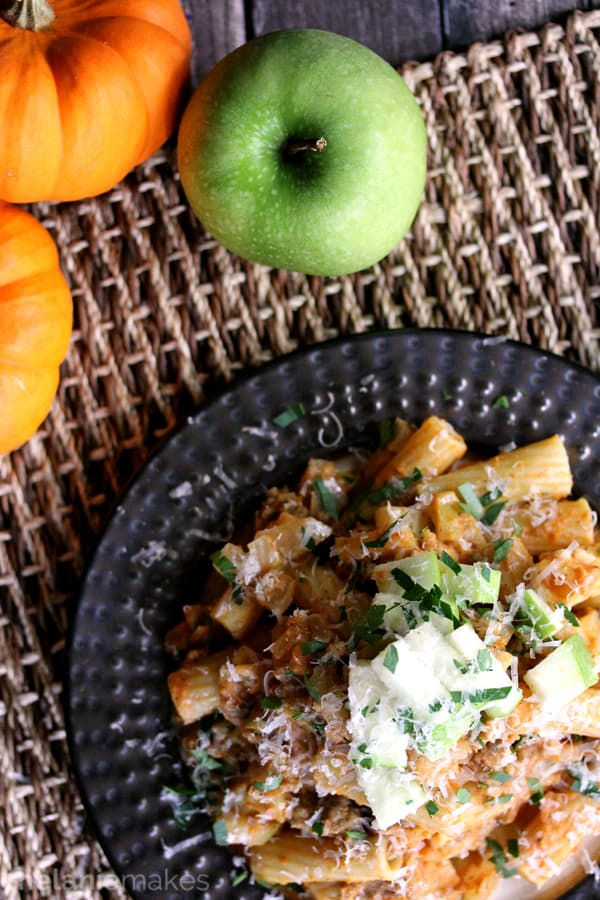 This Pumpkin Pasta with Sausage and Apples has all of your favorite seasonal flavors in one dish.  Sausage, apples and onions stud a rich pumpkin cream sauce flecked with cinnamon and nutmeg.  This mountain of deliciousness is then topped with a blizzard of Parmesan cheese, parsley and additional apple for a picture perfect presentation.