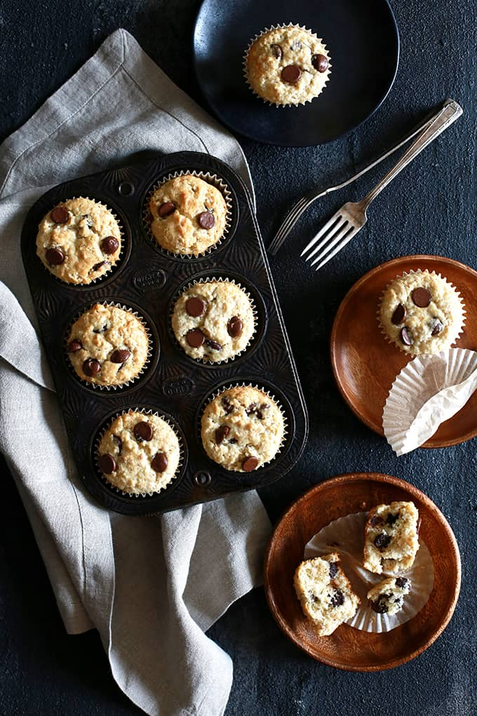 An overhead shot ofOatmeal Chocolate Chip Muffins in a muffin pan and three plates with muffins.