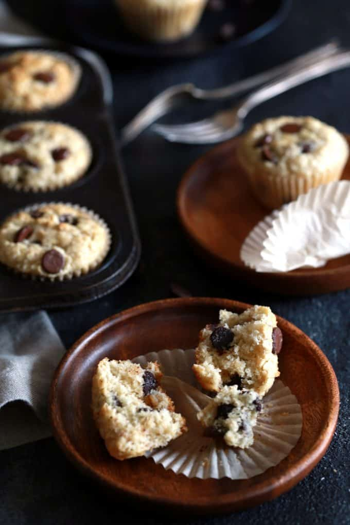 A plate with an Oatmeal Chocolate Chip Muffins with another plate and a muffin pan behind it.