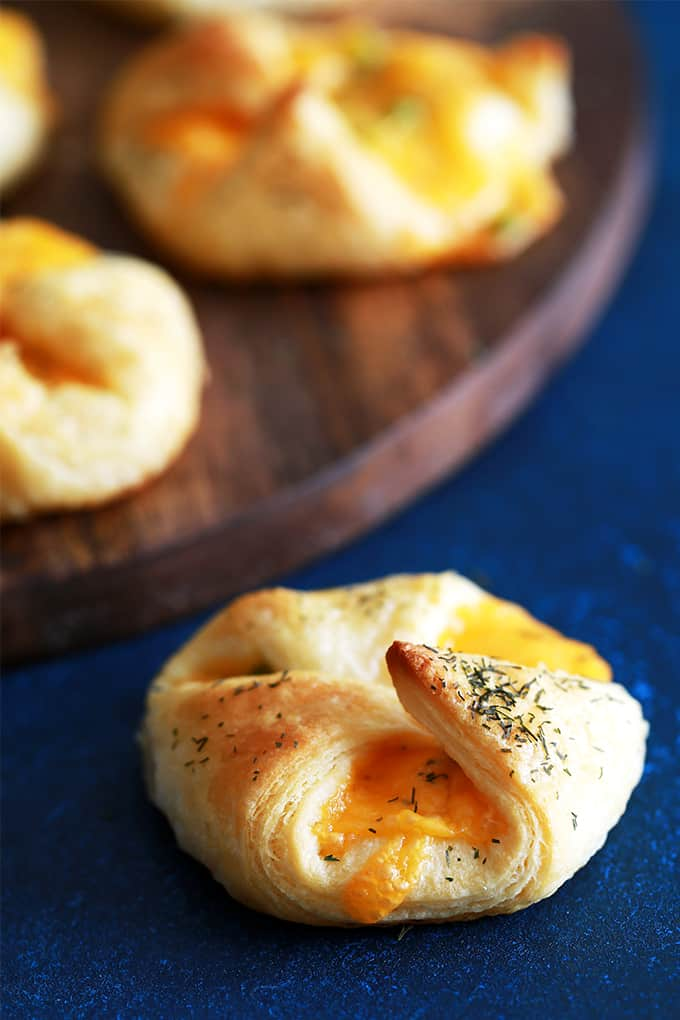 These Mini Cheese and Onion Pastries take only four ingredients and 15 minutes to prepare, a definite no-fuss appetizer or snack.  Sharp cheddar cheese and sliced green onion are gathered in the center of a dill dusted, flaky pastry bundle.