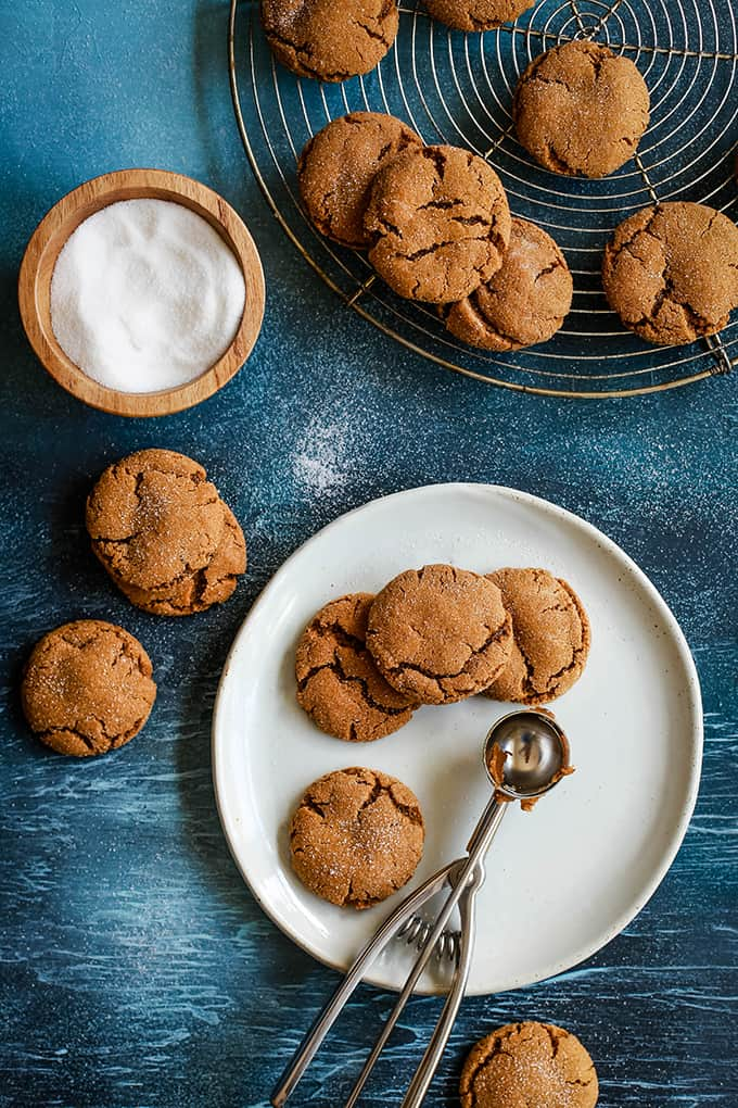 An overhead shot of Soft and Chewy Ginger Cookies sitting on a white plate with a cookie scoop surrounded by additional cookies on a blue surface, a wooden bowl of sugar and a cooling rack of additional cookies.