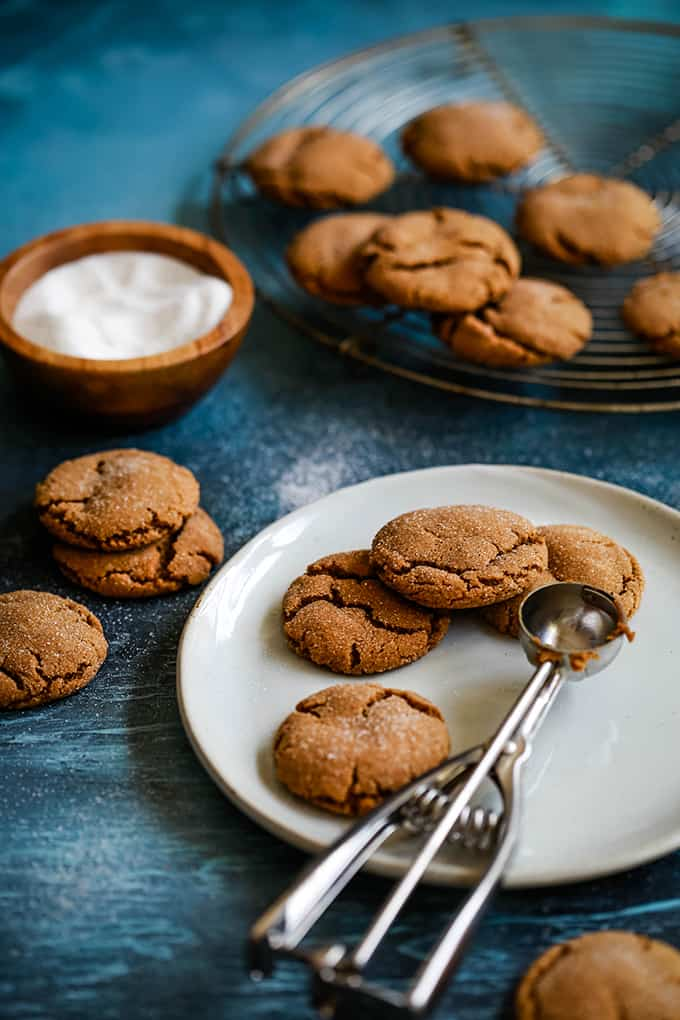 Soft and Chewy Ginger Cookies sit on a white plate with a cookie scoop surrounded by additional cookies on a blue surface, a wooden bowl of sugar and more cookies on a cooling rack.