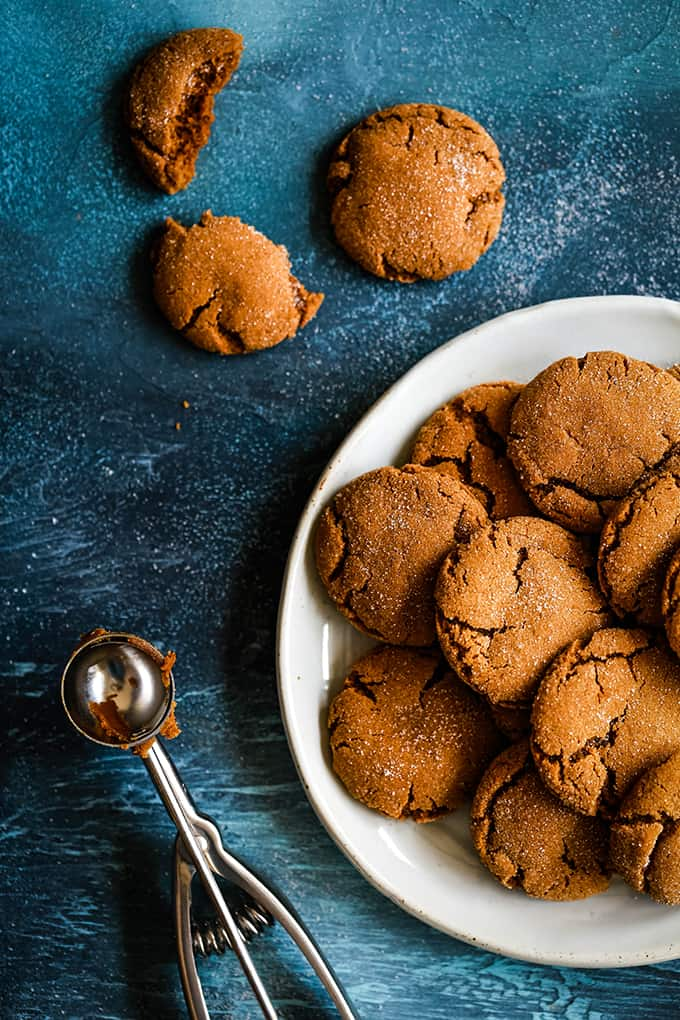 An overhead shot of Soft an Chewy Ginger Cookies on a white plate sitting on a blue background surrounded by a cookie scoop and two additional cookies.