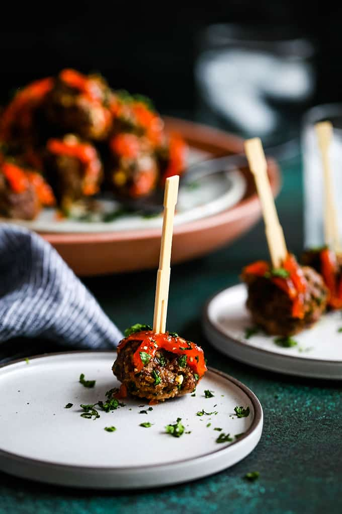 A Chili Garlic Meatball rests on a white plate with additional plates in the background.