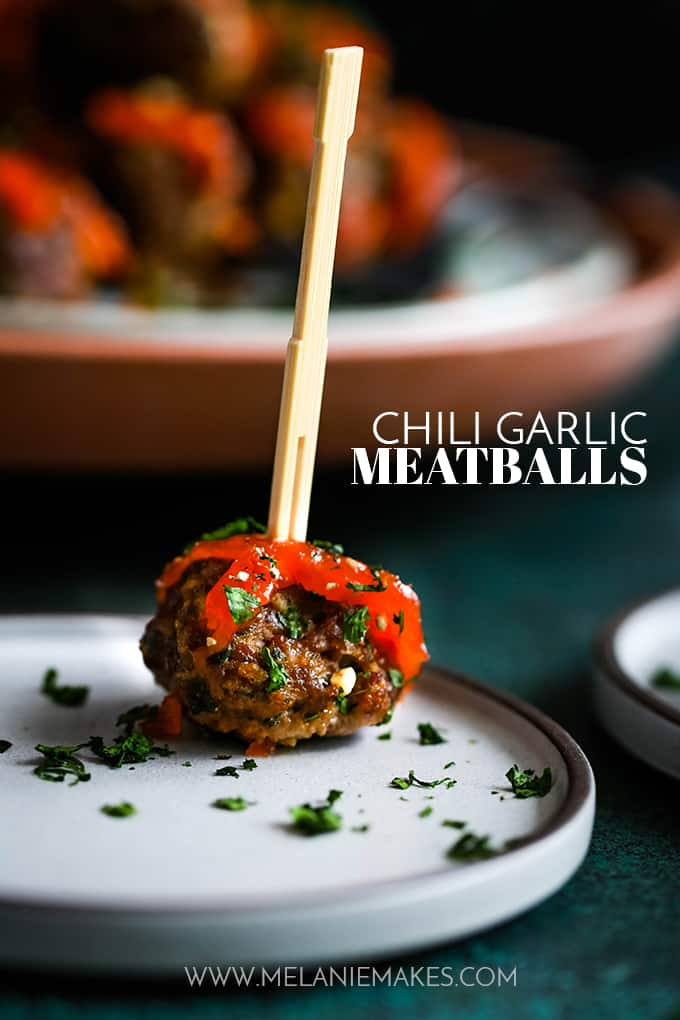 A Chili Garlic Meatball sprinkled with cilantro with a toothpick sits on a white plate.