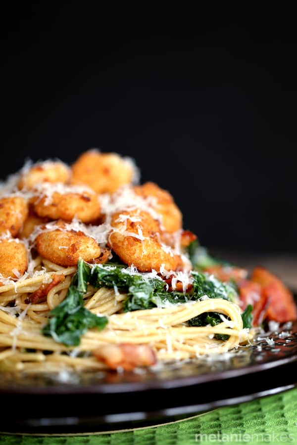This eight ingredient Shrimp, Bacon and Kale Parmesan Pasta makes any dinner special and comes together in just 30 minutes. Your favorite pasta is dressed in balsamic vinegar and olive oil and studded with sauteed sliced onions and chopped kale. Everyone then gets the opportunity to top their bowls with popcorn shrimp, crispy bacon and a shower of Parmesan cheese.