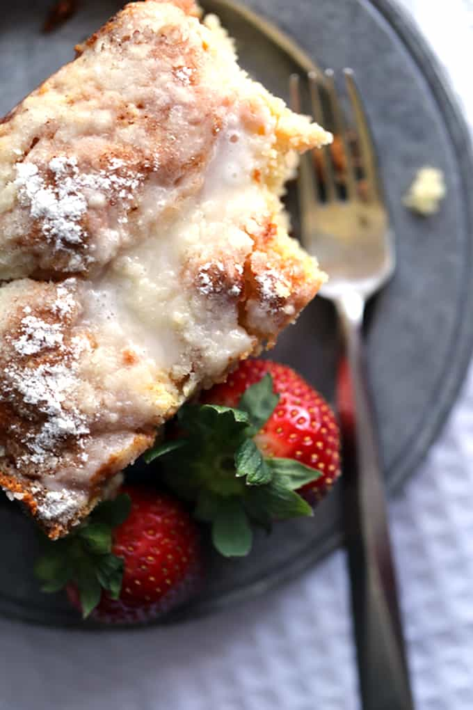This Strawberries and Cream Coffee Cake will have your family rolling out of their beds and making a beeline for the kitchen in record time.  A thick swirl of cream cheese and strawberry jam is sandwiched between two layers of light as air coffee cake.  This breakfast treat is then topped with a sugar and butter topping before being baked and then drizzled with a powdered sugar glaze.