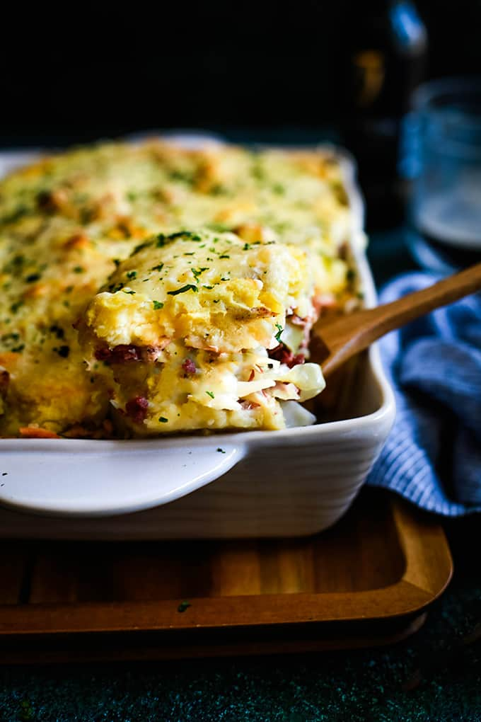 A wooden spoon removes a slice of the Best Reuben Casserole from a white baking dish.