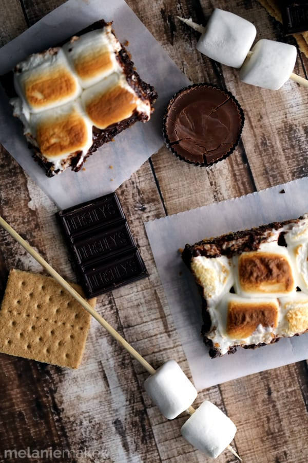 There's no campfire needed for these Peanut Butter Cup Stuffed S'mores Brownies! A thick graham cracker crust base is topped with a rich, chocolate brownie batter, peanut butter cups, dark chocolate candy bar large jet-puffed marshmallows. Decadent and delicious!