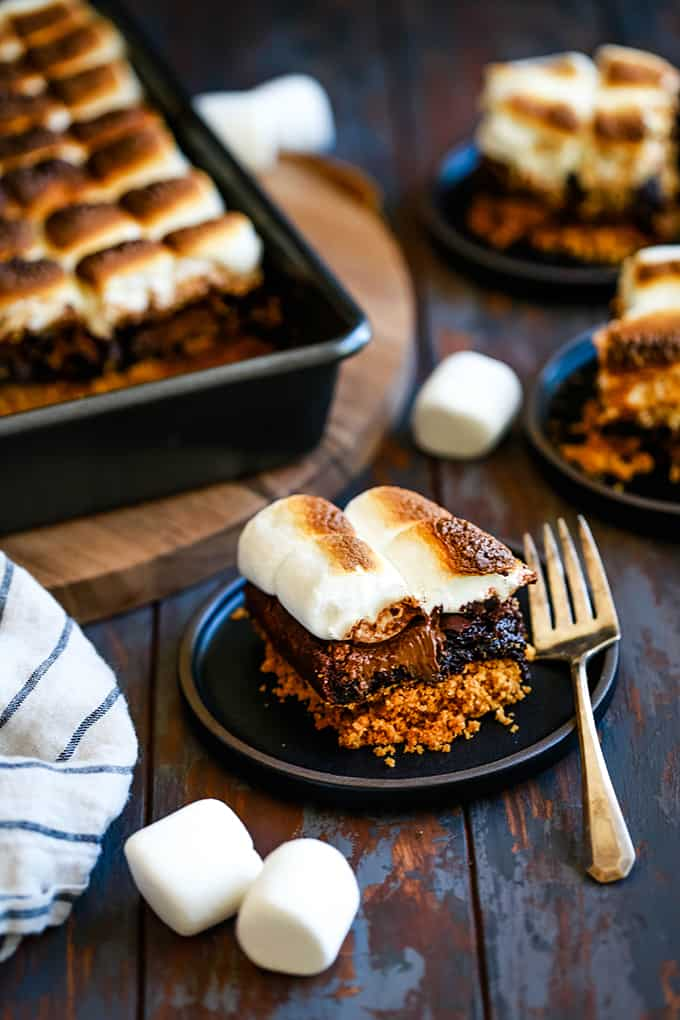 A Peanut Butter Cup Stuffed S'mores Brownie sits on a black plate with other brownies in the background.