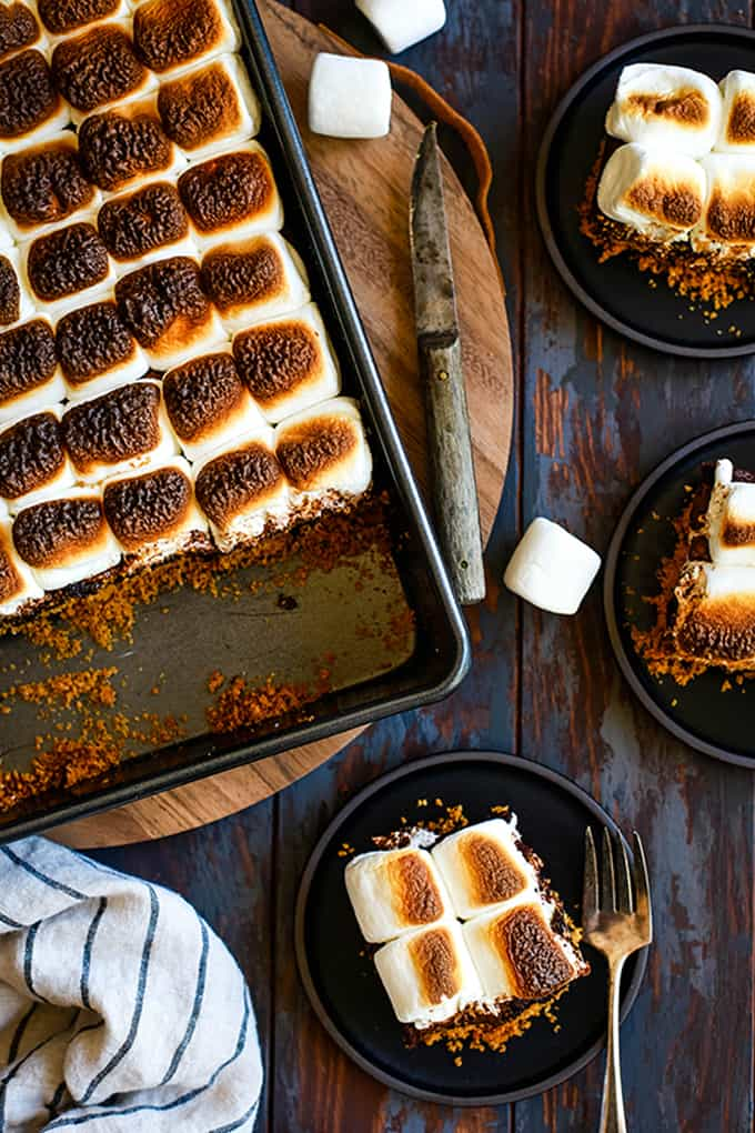 An overhead shot of a pan of Peanut Butter Cup Stuffed S'mores Brownies and three plates each with a brownie on them.