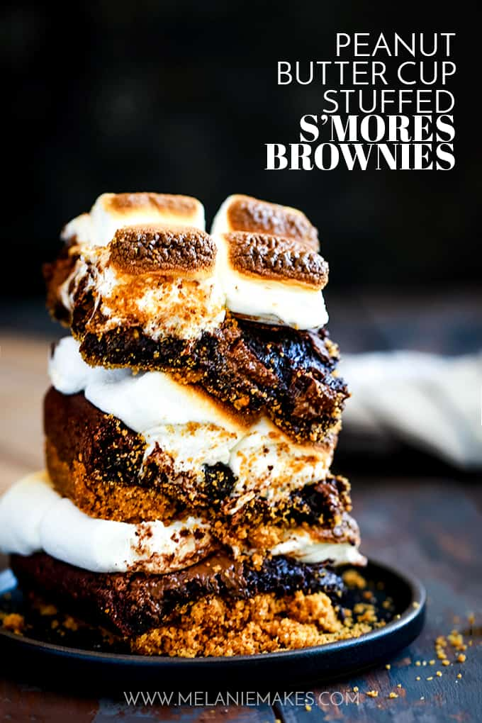 A stack of Peanut Butter Cup Stuffed S'mores Brownies on a black plate.