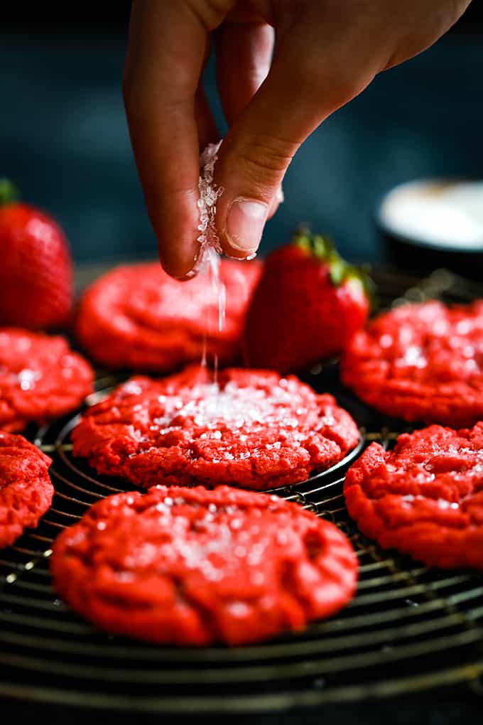 A hand sprinkles sugar onto a Strawberry Sugar Cookie.